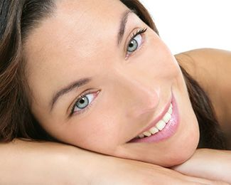 Attractive woman with smooth, youthful skin resting cheek on hand